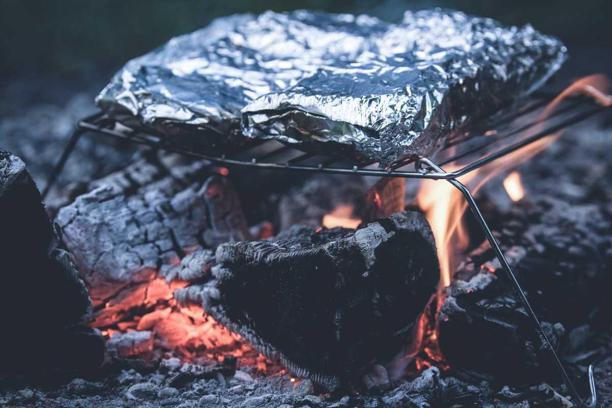 Mat i folie på grillgaller över öppen eld